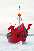 Little red sailing boat in winter