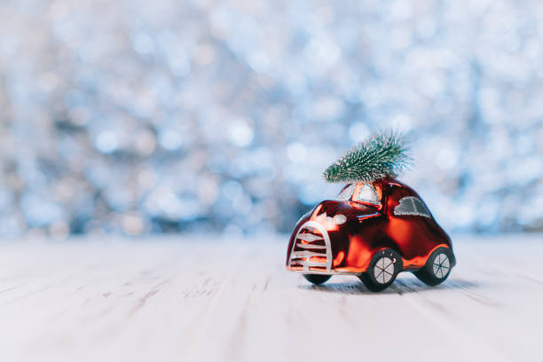 Little red toy car carries a Christmas tree stock photo