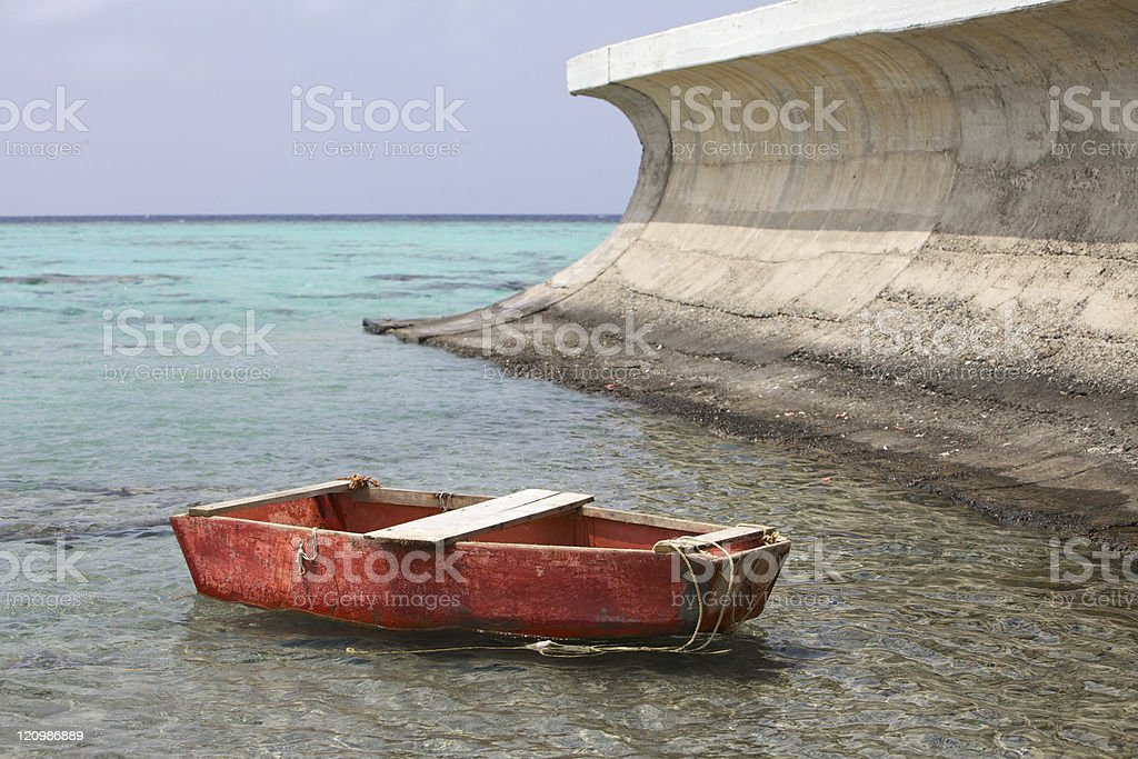 Little red two-oar boat under the concrete wave royalty-free stock photo
