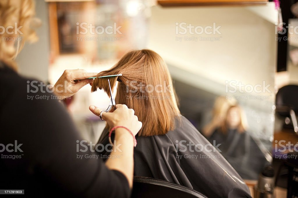 Little Red-Haired Girl Getting Haircut in Salon stock photo