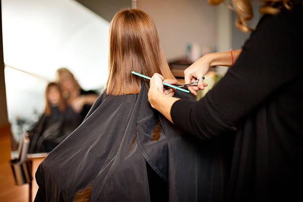 Little Red-Haired Girl Getting Her Hair Cut in Salon stock photo