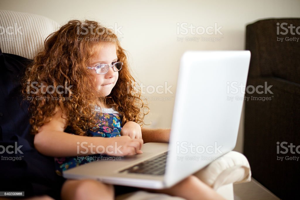 Little Red-Haired Girl Using Laptop Computer at Home stock photo