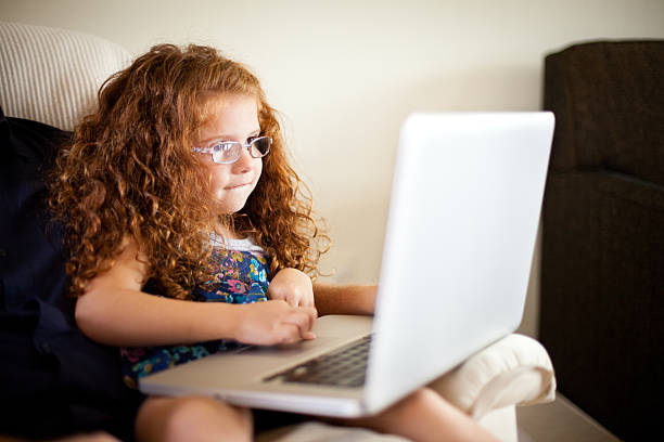 Little Red-Haired Girl Using Laptop Computer at Home