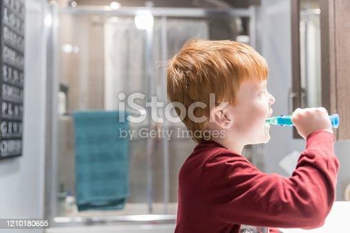 948443044 istock photo Little Redhead Boy Brushing His Teeth 1210180655