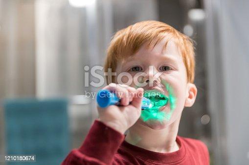948443044 istock photo Little Redhead Boy Brushing His Teeth 1210180674