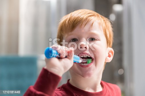 948443044 istock photo Little Redhead Boy Brushing His Teeth 1210181445
