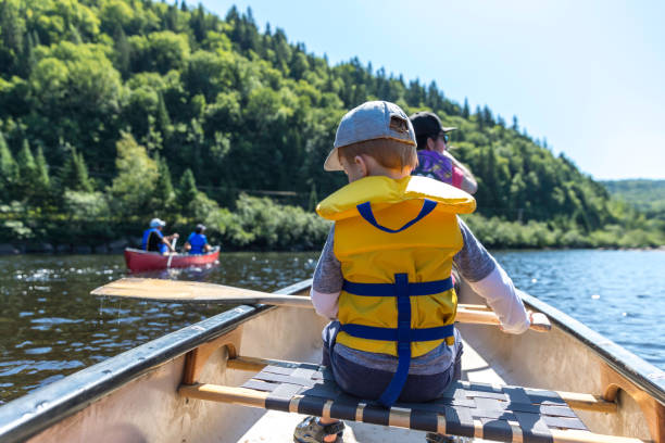 Little Redhead Boy Canoeing with his Family at Parc National de la Jacques Cartier, Quebec, Canada stock photo
