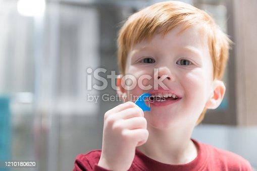 948443044 istock photo Little Redhead Boy Flossing His Teeth 1210180620