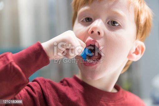 948443044 istock photo Little Redhead Boy Flossing His Teeth 1210180666