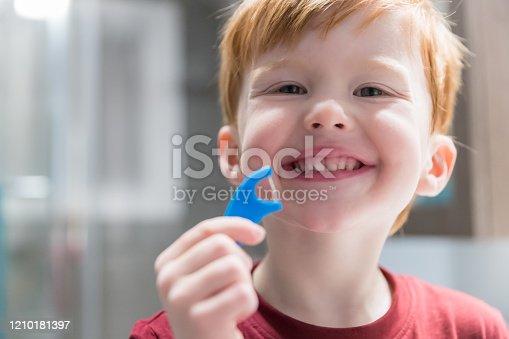 948443044 istock photo Little Redhead Boy Flossing His Teeth 1210181397