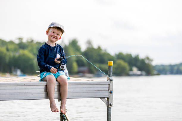 Little Redhead Boy Learning to Fish in Summer stock photo