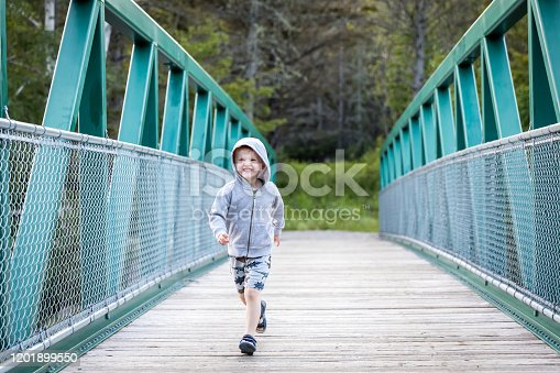 A Little redhead boy is running across a bridge in summer. He is having a lot of fun and laughing. It is a beautiful summer day.