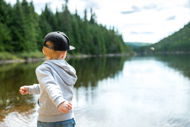 Little Redhead Boy Throwing Rocks In Lake in Summer stock photo