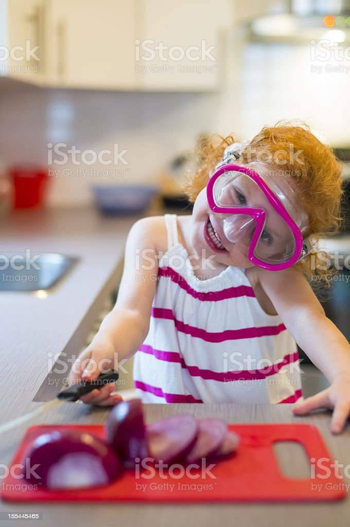 Little redhead wearing a swimming mask to cut onions. stock photo