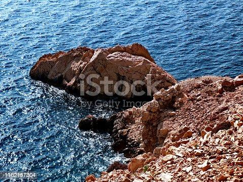 959508862 istock photo Little rock in the sea 1162157304