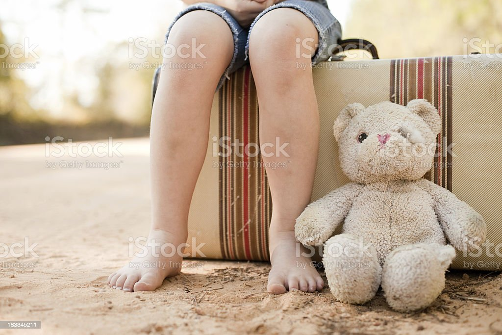 Little Runaway or Homeless Girl with Suitcase and Teddy Bear royalty-free stock photo