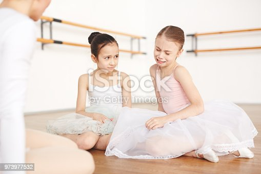 istock Little sad ballerinas sitting on floor in studio 973977532