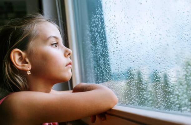 Pequeña chica triste pensativa mirando a través del cristal de la ventana con un montón de gotas de lluvia. Imagen conceptual de la infancia de la tristeza. - foto de stock