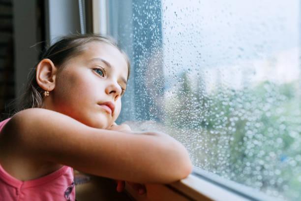 Kleines trauriges Mädchen nachdenklich Blick durch das FensterGlas mit vielen Regentropfen. Traurigkeit Kindheit Konzept Bild. – Foto