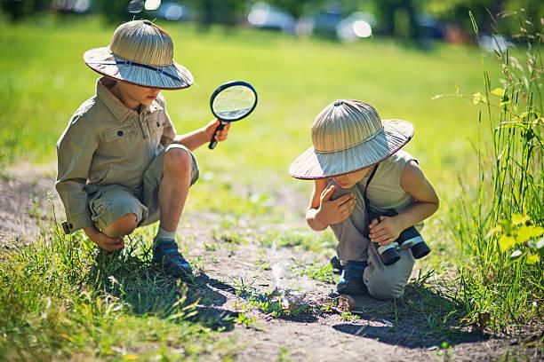 los niños pequeños safari hacer fuego con aumento de vidrio - boy scout fotografías e imágenes de stock