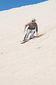 Sandboarding at sand dunes in Little Sahara, Kangaroo Island, South Australia.Focus on the man
