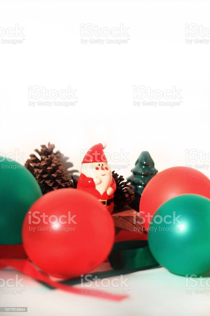 A little Santa Claus ceramic doll is sitting in front of pine cones with red and green bubble around him stock photo