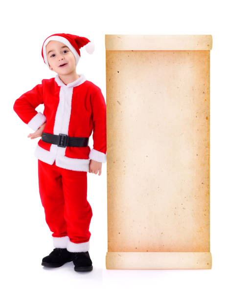 Little Santa Claus standing near big old paper wish list stock photo