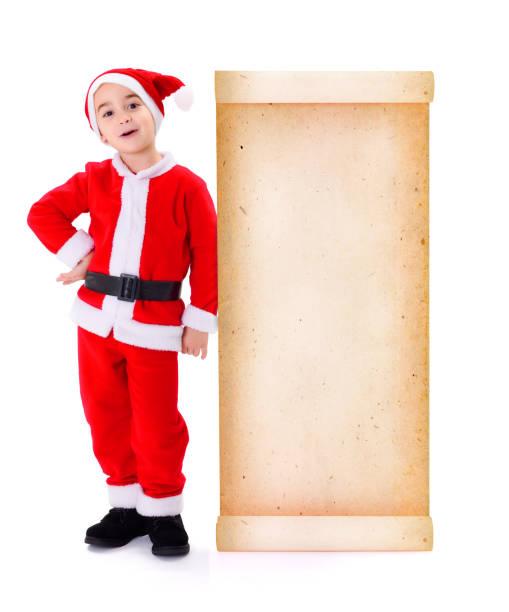 Little Santa Claus standing near big old paper wish list