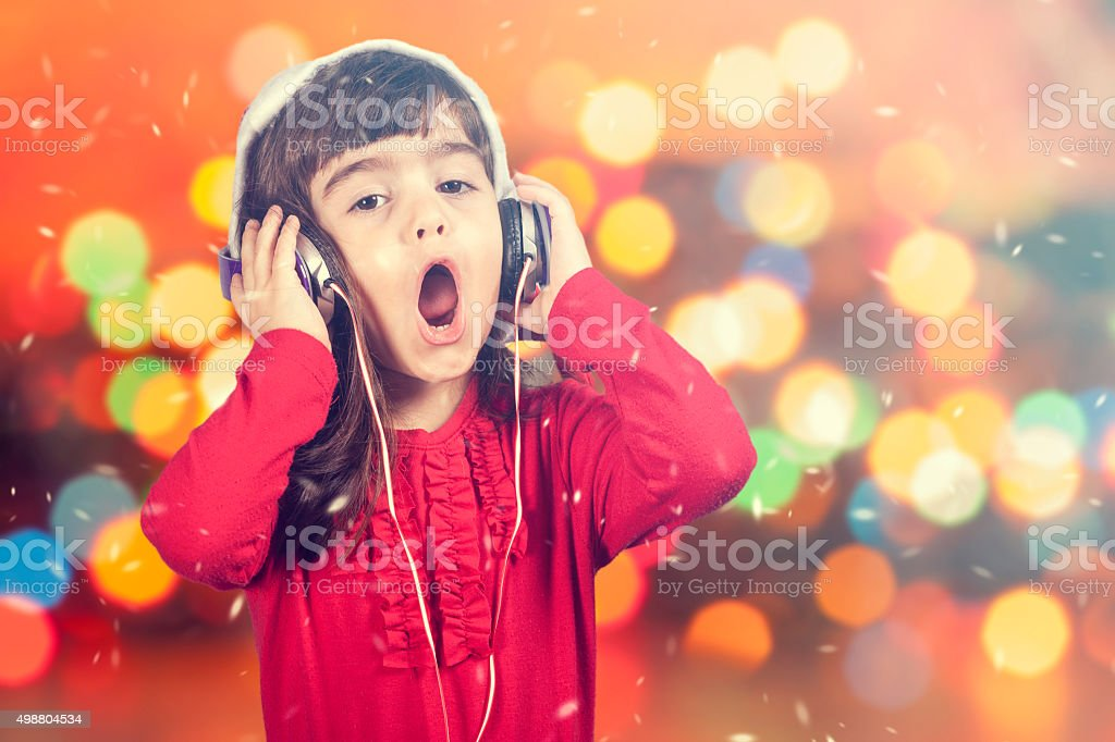 Little Santa girl singing while listening to music stock photo