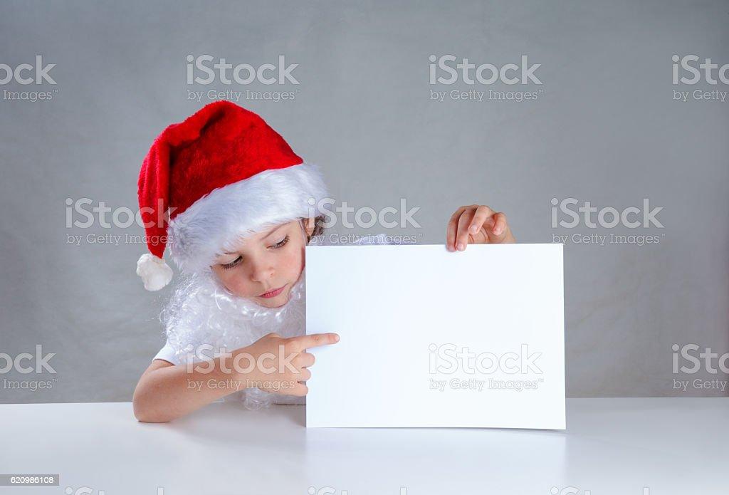 Little Santa peeping from behind white envelope looks at him foto royalty-free