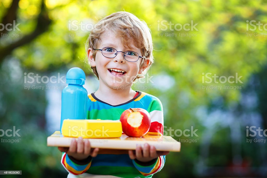 little school boy with books, apple and drink bottle stock photo