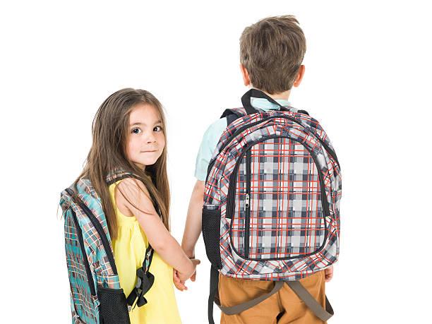 kleine schule mädchen und jungen gehen hand in hand - liebeskind umhängetasche stock-fotos und bilder