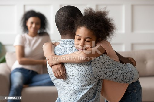 istock Little school girl embracing mixed race father. 1199968751
