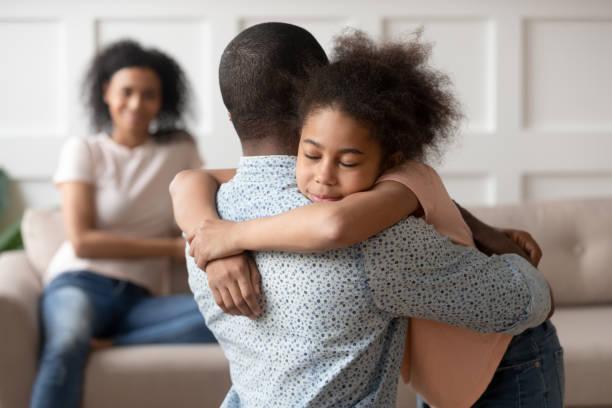 liten skolflicka omfamna blandad ras far. - förälder bildbanksfoton och bilder