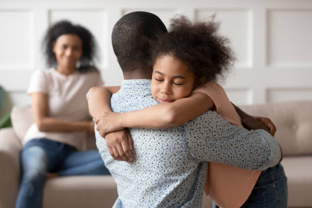 Little school girl embracing mixed race father. Young african american man holding, embracing, comforting smiling happy calm black cute kid daughter, blurred mother sitting on couch on background, loving supporting family concept. parent stock pictures, royalty-free photos & images