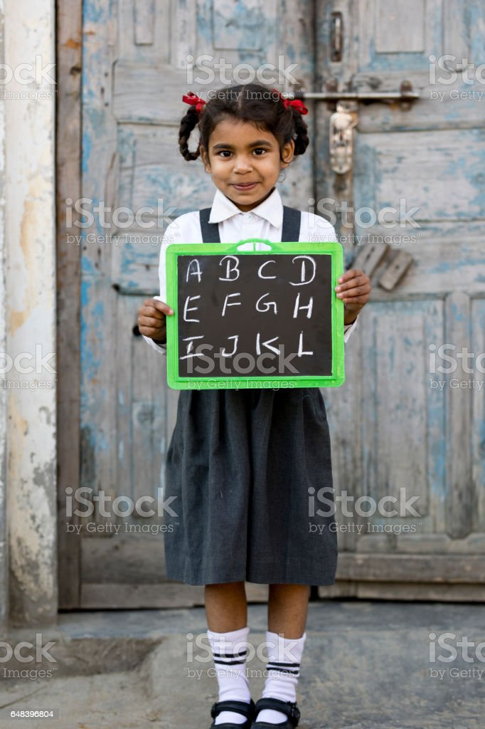 Little school girl holding slate stock photo