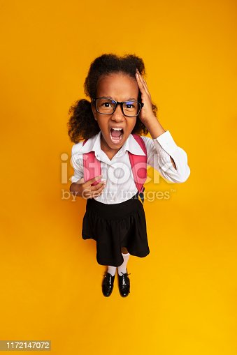 istock Little School Girl Shouting Touching Head On Yellow Background 1172147072