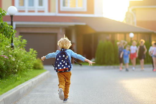 Little schoolboy joyfully running to school after holiday. Child meeting with friends. Education for children. Back to school concept. Kids friendship.