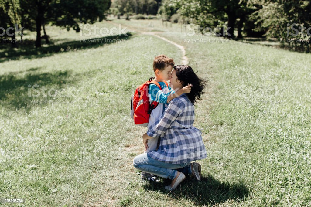 Little schoolboy kissing and hugging his mother saying goodbye to her stock photo
