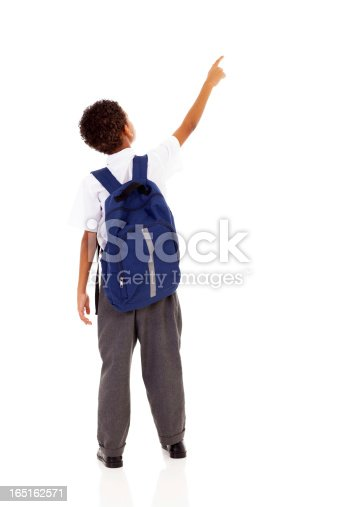 istock little schoolboy with schoolbag pointing 165162571