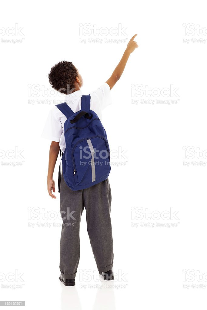 little schoolboy with schoolbag pointing stock photo