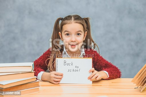 istock A little schoolgirl on a gray background. Hold text paper back to school. Look into the camera. 1153881896