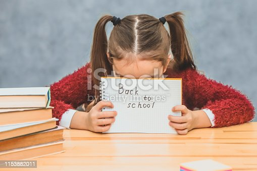 istock A little schoolgirl on a gray background. Hold the paper with the text back to school. Having let his head down, the girl hid herself. 1153882011