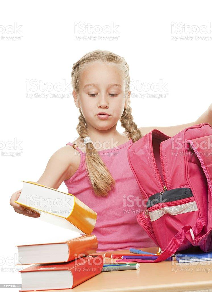 Little schoolgirl packing her rucksack royalty-free stock photo