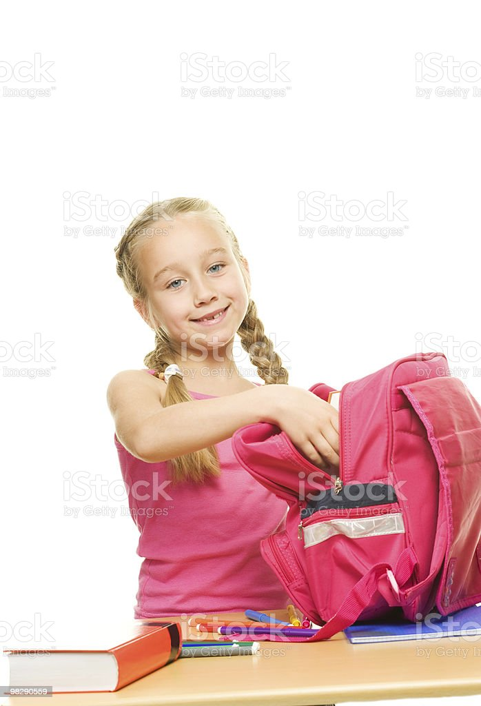 Little schoolgirl packing her rucksack royalty-free stock photo