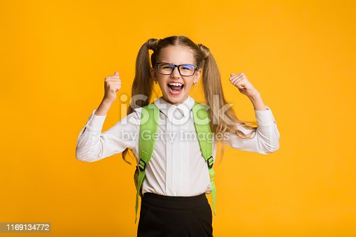 1176772377 istock photo Little Schoolgirl Shouting Loudly Rejoicing Victory On Yellow Background 1169134772