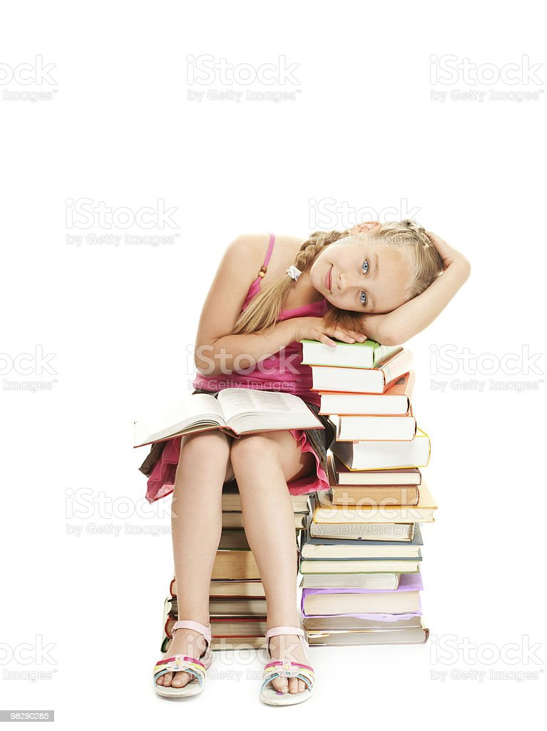 Little schoolgirl sitting on a stack of books royalty-free stock photo