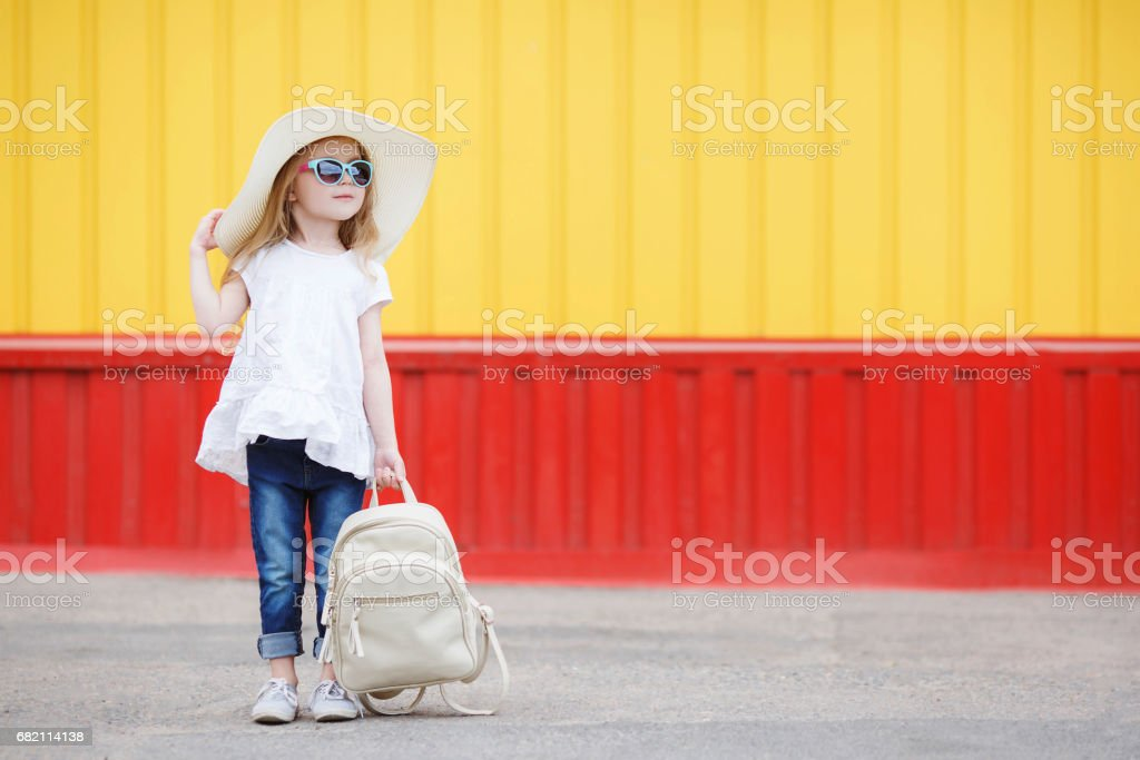 Little schoolgirl with a white backpack stock photo