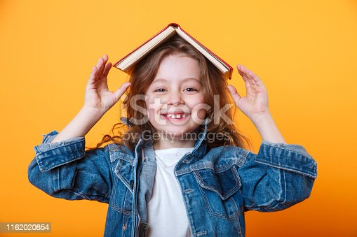 istock little schoolgirl with book on her head, wearing jeans jacket and black eyeglasses, standing against yellow background. 1162020854