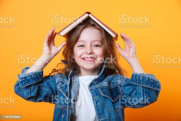 Little schoolgirl with book on her head wearing jeans jacket and picture id1162020854?b=1&k=6&m=1162020854&s=612x612&h=bw9cjicfwj3hdntfyugelmkkq wxapig9ohvyikil u=